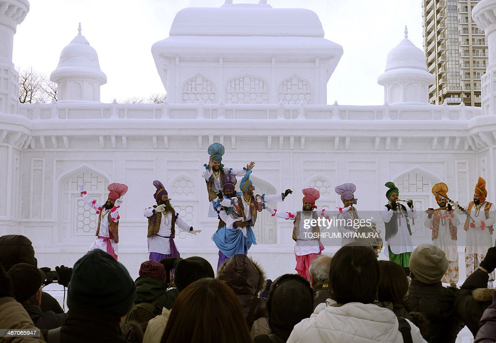 Visitors watch Indian dancers performing a Bhangra dance at the stage in front of the large snow sculpture of 'Tomb of Itmad-ud-Daula' of India during the 65th annual Sapporo Snow Festival in Sapporo on February 6, 2014. Nine foreign teams compete in the contest among some two million tourists expected to visit the week-long festival which started on Februrary 5.