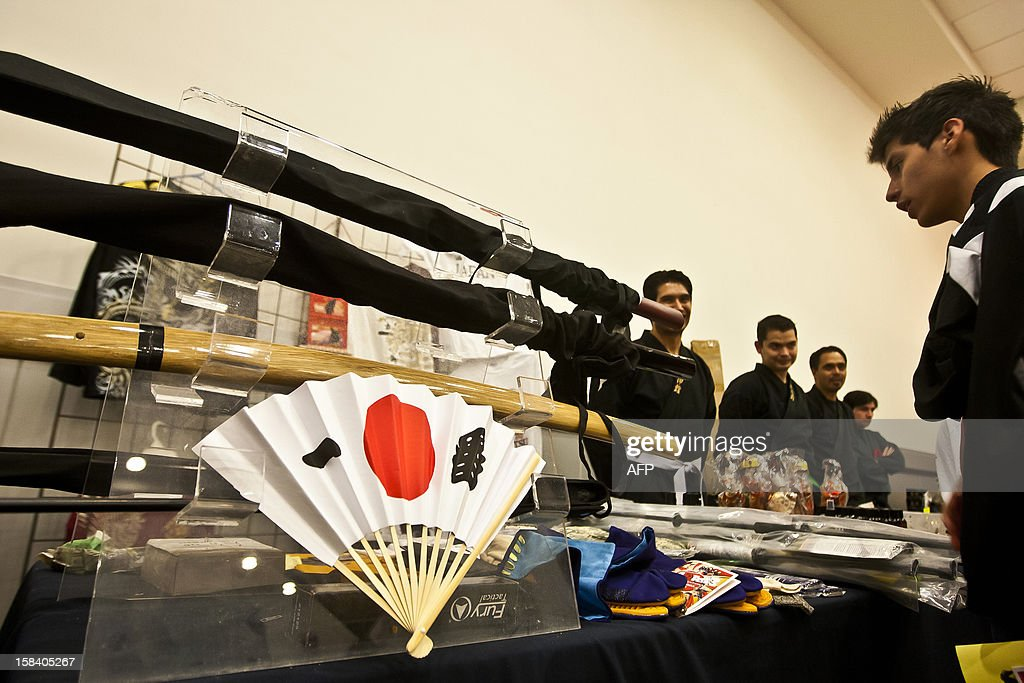 Visitors watch Japanese swords used in the XV century at the 'Japan and its Ancestral Warriors' exhibition, in Monterrey, Mexico on December 15, 2012. AFP PHOTO/Julio Cesar Aguilar