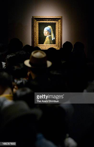Visitors watch Johannes Vermeer's 'Girl with a Pearl Earring' at the 'Masterpieces from the Royal Picture Gallery Mauritshuis' exhibition atthe Tokyo...