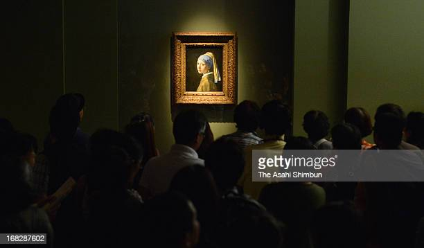 Visitors watch Johannes Vermeer's 'Girl with a Pearl Earring' at the 'Masterpieces from the Royal Picture Gallery Mauritshuis' exhibition at Kobe...