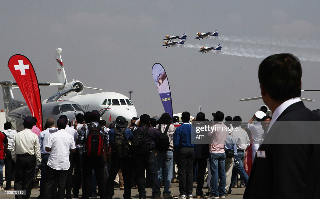 Visitors watch members of The Flying Bulls aerobatics team from the Czech Republic fly in formation in their Zlin Z-50's during the second day of the ongoing 9th Edition of Aero India Show 2013 in Bangalore on February 7, 2013. India, the world's leading importer of weaponry, is hosting one of Asia's biggest aviation trade shows with Western suppliers eyeing lucrative deals and a Chinese delegation attending for the first time.
