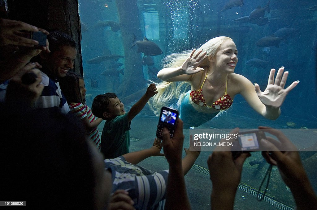 Visitors watch Mirella Ferraz, known as Brazilian mermaid, as she swims with fish in a giant tank during a show at an aquarium in Sao Paulo, Brazil, on February 10, 2013. AFP PHOTO / Nelson ALMEIDA