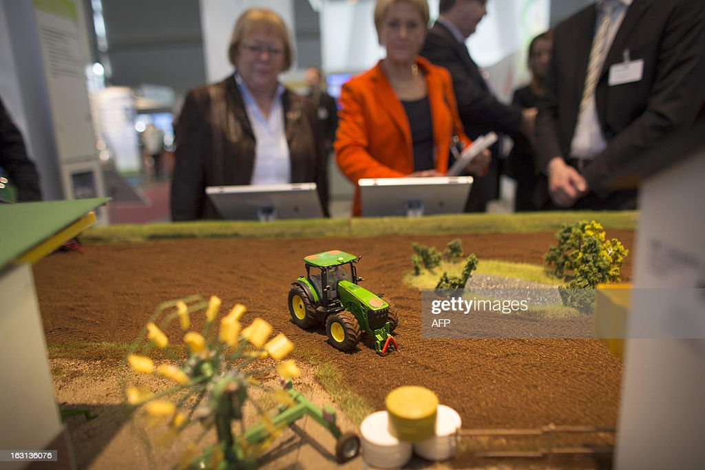 Visitors watch models of electronically controlled tractors during a demonstration at Fraunhofer institute stand at the 2013 CeBIT technology trade fair on March 5, 2013 in Hanover, Germany. CeBIT will be open March 5-9. AFP PHOTO / CARSTEN KOALL