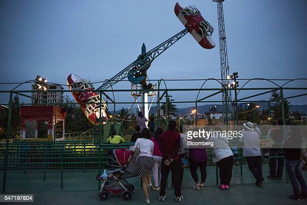 Visitors watch other guests on a carnival ride at the National Amusement Park known as the Children's Park in Ulaanbaatar Mongolia on Wednesday July...