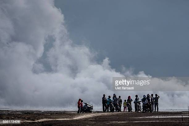 Visitors watch smoke emerge from the mudflow during the tenth anniversary of the mudflow eruption on May 29 2016 in Sidoarjo East Java Indonesia On...