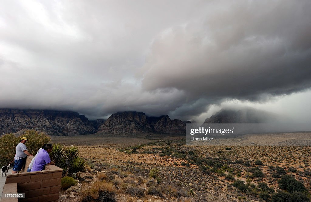 Visitors watch storm clouds at the Red Rock Canyon National Conservation Area on August 25, 2013 near Las Vegas, Nevada. Moisture from Tropical Storm Ivo is causing heavy rains and flooding in parts of the Las Vegas Valley.