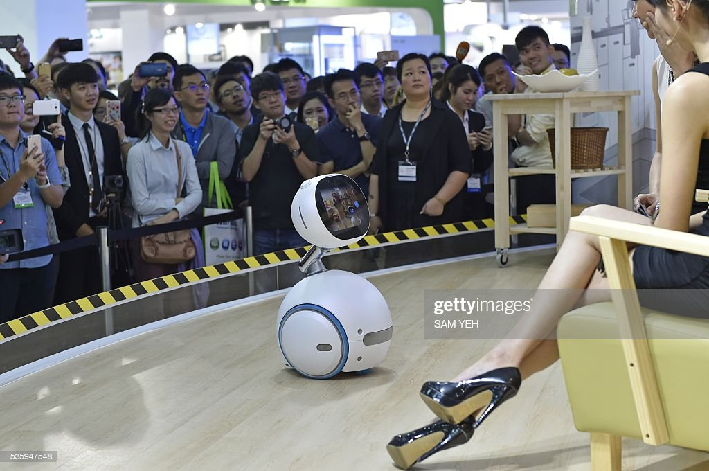 Visitors watch the ASUS Zenbo robot during the annual Computex computer exhibition on May 31, 2016. More then 5,000 booths from thirty countries take part in COMPUTEX Show between May 31 to June 4. / AFP / SAM YEH