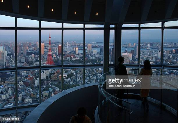 Visitors watch the cityscape of Tokyo during the press preview of Tokyo City View sightseeing floor of Roppongi Hills on March 11 2003 in Tokyo Japan