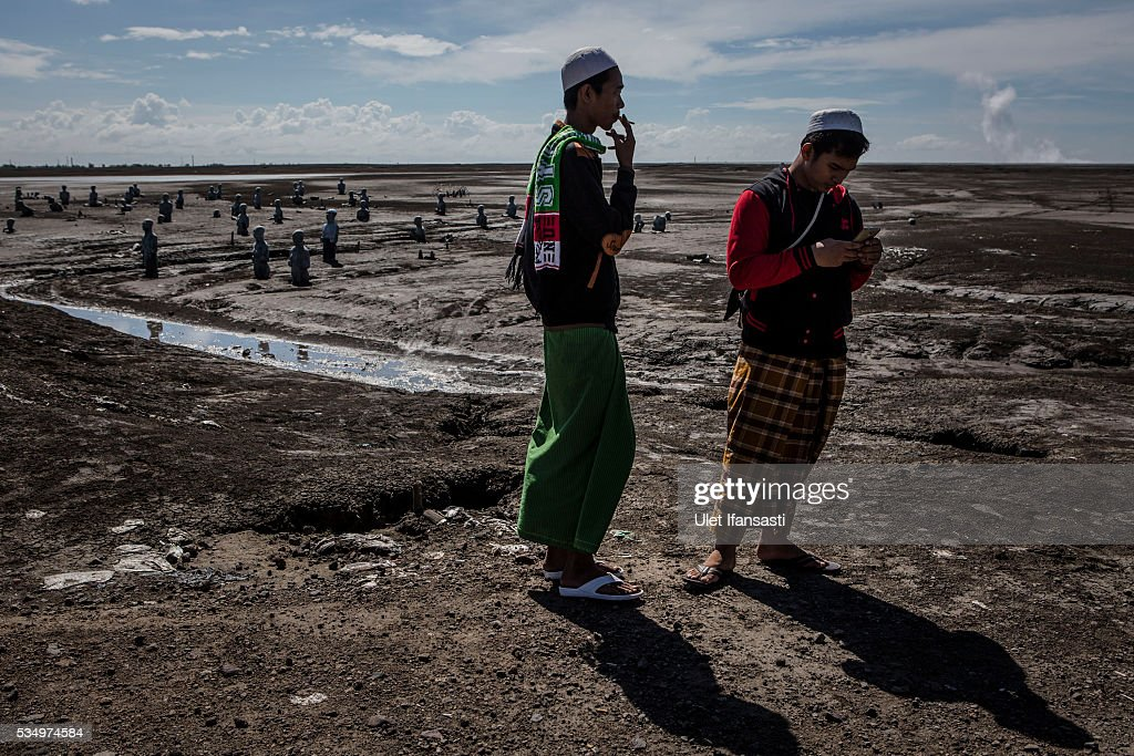 Visitors watch the mudflow on May 27, 2016 in Sidoarjo, East Java, Indonesia. Residents of villages that were damaged by the Sidoarjo mudflow and residents received compensation, after almost ten years, from the Indonesian oil and gas company, PT Lapindo Brantas. The mudflow eruption is suspected to have been triggered by the drilling activities of oil and gas company, though they refute the claims, instead blaming a 6.3 magnitude earthquake that struck a neighboring city two days before the mudflow eruption. The earthquake struck Yogyakarta on May 27th, 2006, a city 150 miles west of a drill site in Sidoarjo, two days before the mudflow eruption. According to reports, twenty lives were lost and nearly 40,000 people displaced, with damages topping $2.7 billion. Ten years since the eruption, the mud geysers continue to spurt daily and high levels of heavy metals have been detected in nearby rivers.