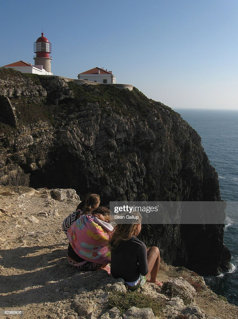 Visitors watch the sun set next to Cabo Sao Vicente lighthouse on the most southwestern tip of Europe on July 30 2008 near Sagres Portugal Portugal...