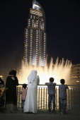 Visitors watch the water show in the Dubai Fountain in front of The Address Burj Dubai Lake Hotel on April 9 2014 in Dubai United Arab Emirates The...