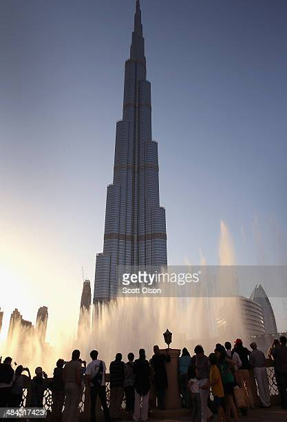 Visitors watch the water show in the Dubai Fountain in front of the Burj Khalifa on April 9 2014 in Dubai United Arab Emirates At 2722 ft the Burj...