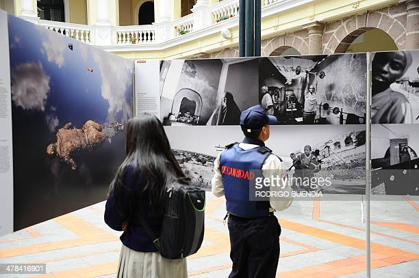 Visitors watch the World Press Photo 2013 exhibition in Quito on March 13 2014 AFP PHOTO / RODRIGO BUENDIA