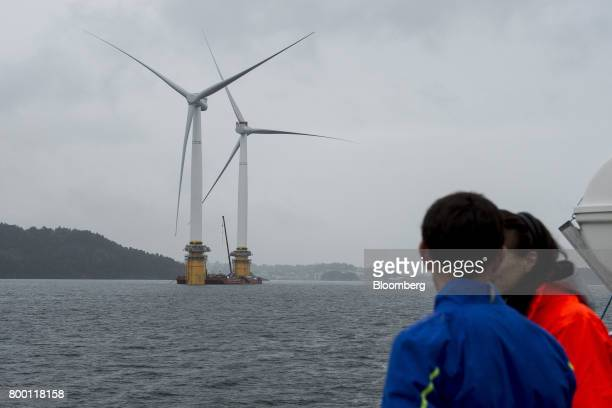 Visitors watch two offshore floating wind turbines being assembled in the Hywind pilot park operated by Statoil ASA in Stord Norway on Friday June 23...