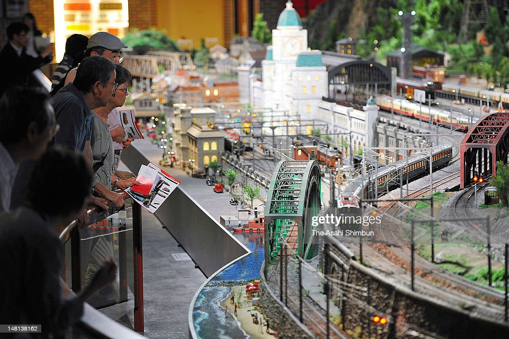 Visitors watches the model trains running in the diorama at Hara Model Railway Museum on July 10, 2012 in Yokohama, Kanagawa, Japan. The museum is displaying the 1,000 private collections of Nobutaro Hara.