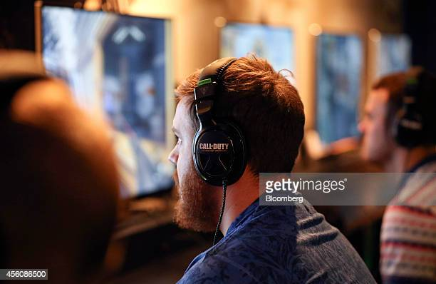 Visitors wear headsets as they play the 'Call of Duty Advanced Warfare' video game produced by Activision Blizzard Inc on Microsoft Corp Xbox One...