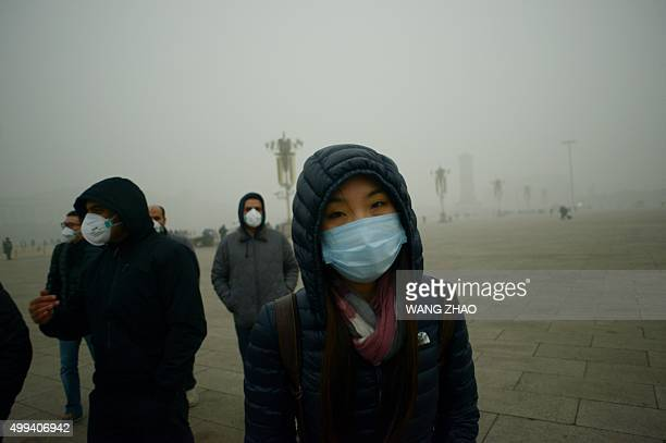 Visitors wear masks as they walk in Tiananmen Square during heavy pollution in Beijing on December 1 2015 Beijing ordered hundreds of factories to...
