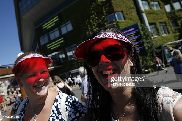 Visitors wear Union Flagthemed sun visors as they pose for a photograph day two of the 2015 Wimbledon Championships at The All England Tennis Club in...