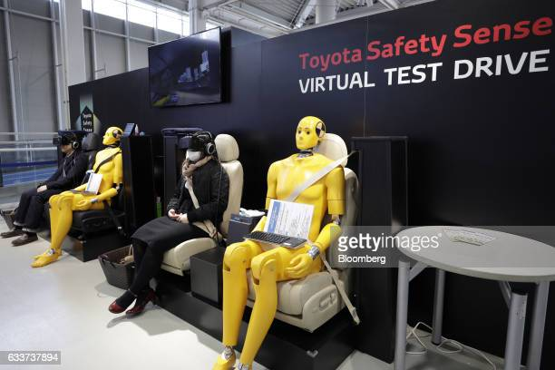 Visitors wear virtual reality headsets as they try the virtual test drive inside the Toyota City Showcase exhibit at the Toyota Motor Corp Mega Web...