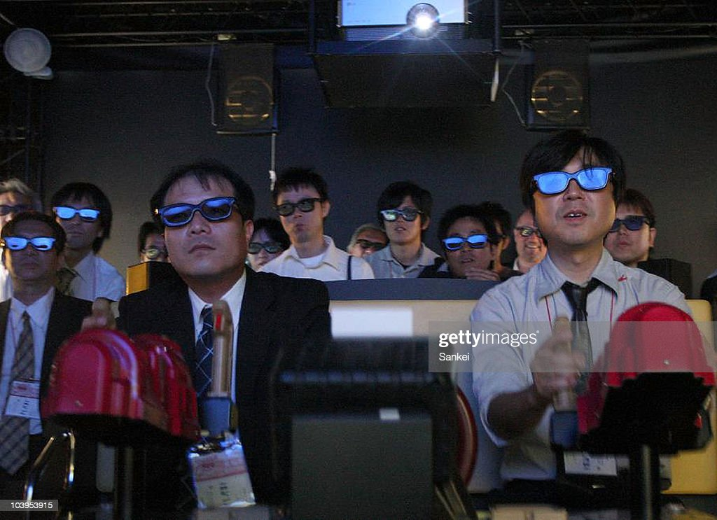 Visitors wearing 3D glasses try Bandai Namco holdings' 'Deadstorm Pirates' during the 48th Amusement Machine Show at Makuhari Messe on September 9, 2010 in Chiba, Japan. The show, open until September 11, is for arcade video game machine industry, whose size of market has been shrinking year by year.