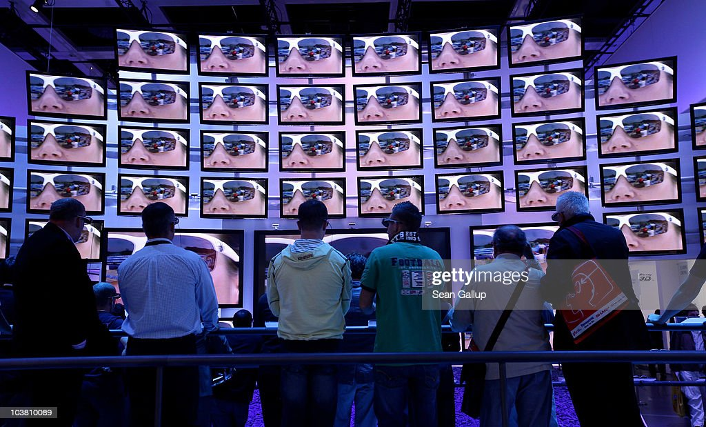 Visitors wearing 3D glasses watch a presentation on 3D televisions at the Panasonic stand at the 2010 IFA technology and consumer electronics trade...