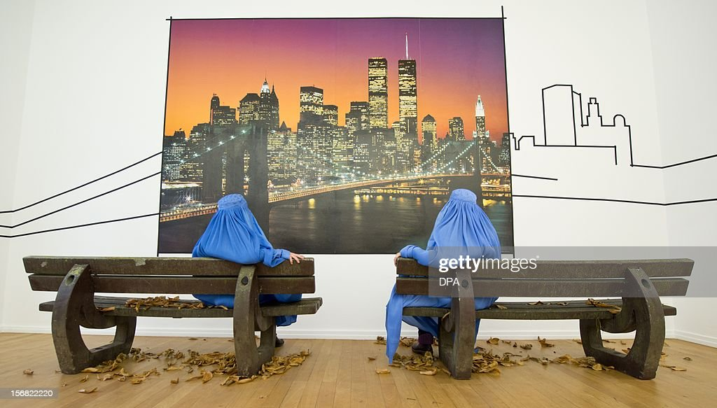 Visitors wearing burkas, sit in front of a photograph of the German artist Naneci Yurdaguel, which shows the skyline of New York and the World Trade Center on November 22, 2012 during the exhibition 'Burquoi' in Wiesbaden, southwestern Germany. One focus of Yurdaguel's artistic engagement is topics on national and religious identity, migration, social exclusion, cultural appropriation and mistrust. They are constantly picked up and are treated critically, often in relation to current public debates, to intervene in social discourse.