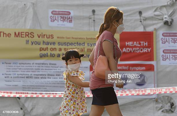 Visitors wearing masks walk in front of a health advisory sign about the MERS virus at a quarantine tent for people who could be infected with the...