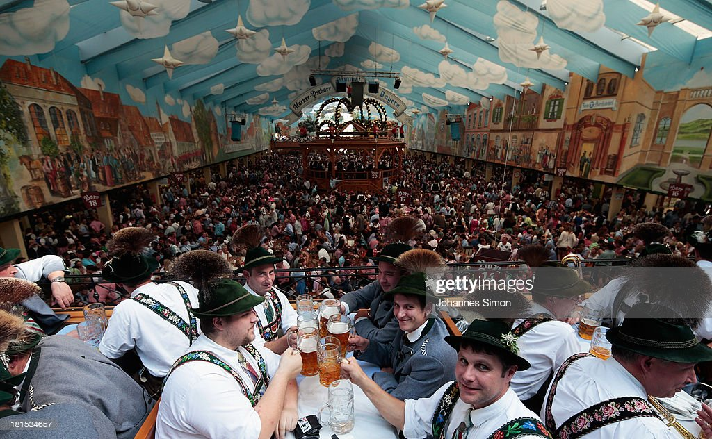 Visitors wearing traditional Bavarian clothes and Gamsbart hat clink beer glasses in the HackerPschorr tent at the Oktoberfest 2013 beer festival at...