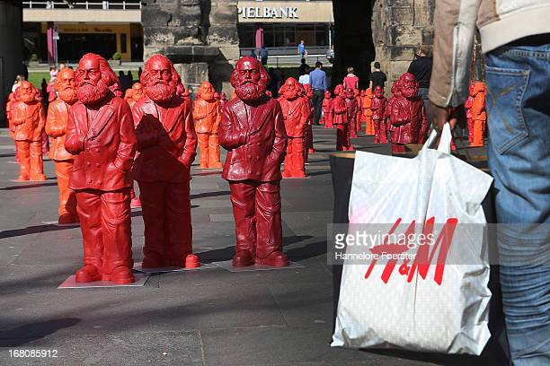 Visitors with a HM bag walk among some of the 500 one meter tall statues of German political thinker Karl Marx on display on May 5 2013 in Trier...