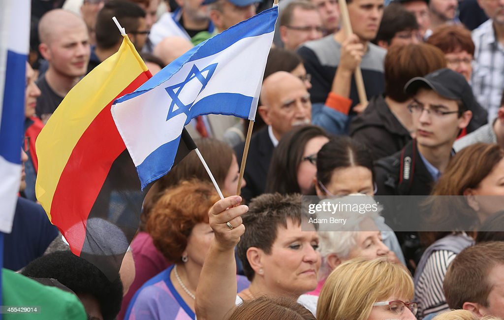 Visitors with Israeli and German flags attend a rally against antisemitism on September 14 2014 in Berlin Germany With the slogan 'Stand Up Never...