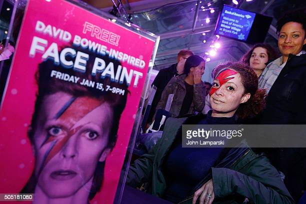 Visitors with painted faces are seen as Bryant Park's Bank of America Winter Village honors David Bowie at Bryant Park on January 15 2016 in New York...