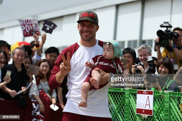 Vissel Kobe new player Lukas Podolski holds a Japanese baby as pose a picture during the welcome ceremony at the Kobe Airport on July 6 2017 in Kobe...