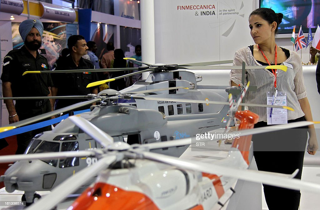 Vistors look at scaled down models of Indian armed forces helicopters at a stall on the fifth and final day of Aero India 2013 at Yelahanka Air Force station in Bangalore on February 10, 2013. India, the world's leading importer of weaponry, opened one of Asia's biggest aviation trade shows February 6 with Western suppliers eyeing lucrative deals and a Chinese delegation attending for the first time. AFP PHOTO