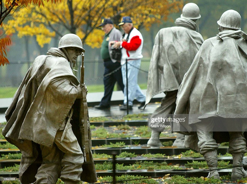 Vistors walk past statues of a soldier at the Korean War Memorial on Veterans Day November 11 2002 in Washington DC