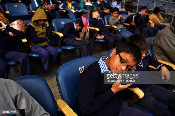 A visually impaired Indian child listens to commentary of the India versus Australia cricket Test match over his portable radio as he and others wait...