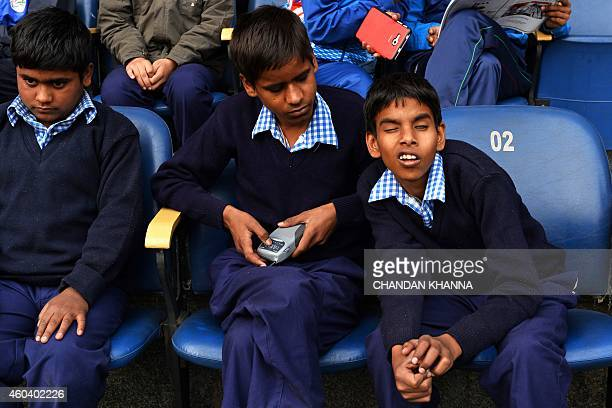 Visually impaired Indian children listen to commentary of the India versus Australia cricket Test match over his portable radio as he and others wait...