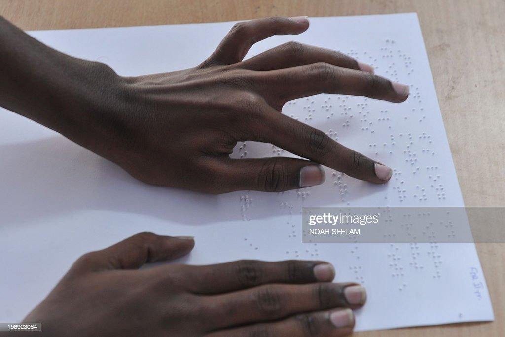 A visually impaired Indian student reads using the Braille system at the Sai Junior College For The Blind in Hyderabad on January 4, 2013, on the 204th birth anniversary of its French inventor Louis Braille. The Braille system is a world-wide system used by visually impaired people for reading and writing. India counts about one third of the world's total blind population. AFP PHOTO/Noah SEELAM
