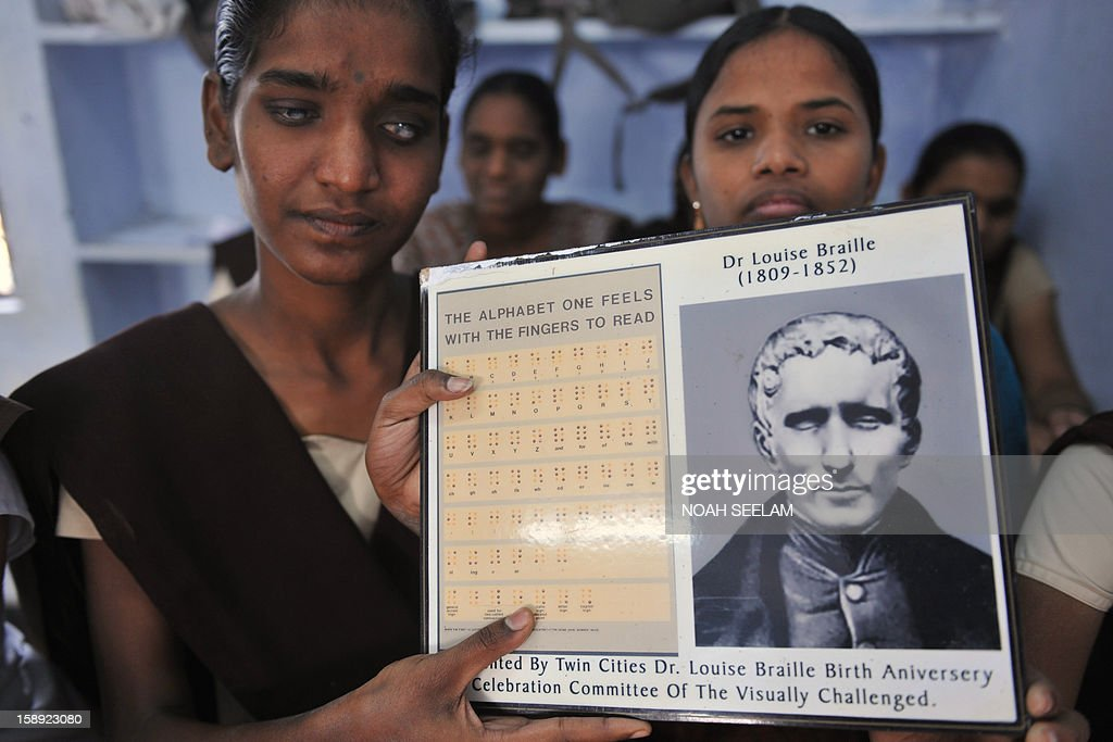 Visually impaired Indian students pose with a portrait of Louis Braille and the Braille alphabets of his invention at the Sai Junior College For The Blind in Hyderabad on January 4, 2013, on the 204th birth anniversary of its French inventor Louis Braille. The Braille system is a world-wide system used by visually impaired people for reading and writing. India counts about one third of the world's total blind population. AFP PHOTO/Noah SEELAM