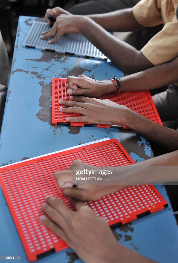Visually impaired Indian students write using the Braille system at the Sai Junior College For The Blind in Hyderabad on January 4, 2013, on the 204th birth anniversary of its French inventor Louis Braille. The Braille system is a world-wide system used by visually impaired people for reading and writing. India counts about one third of the world's total blind population. AFP PHOTO/Noah SEELAM