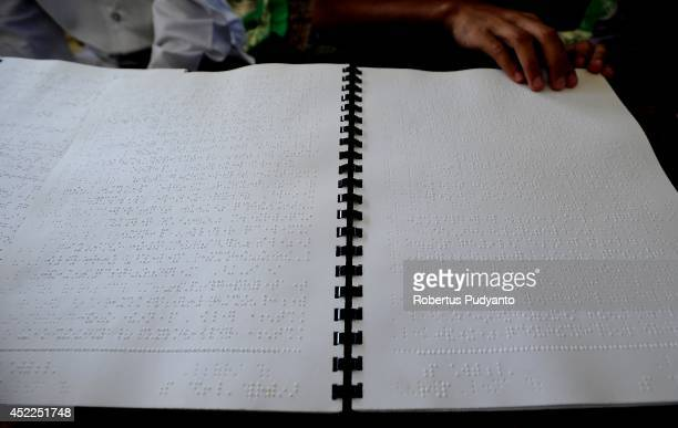 A visually impaired student reads a Braille Quran at The Foundation for The Education of Blind Children on July 17 2014 in Surabaya Indonesia Braille...