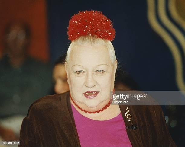 Vita Helen *Schauspielerin Kabarettistin Saengerin D/Schweiz Portrait mit rotem Kopfschmuck roter Halskette und einer Brosche in Form eines...