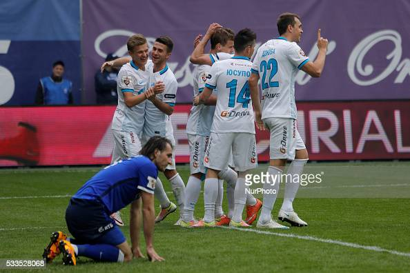 Vitali Dyakov of FC Dynamo Moscow reacts as Artem Dzyuba of FC Zenit St Petersburg celebrates his goal with teammates during the Russian Football...