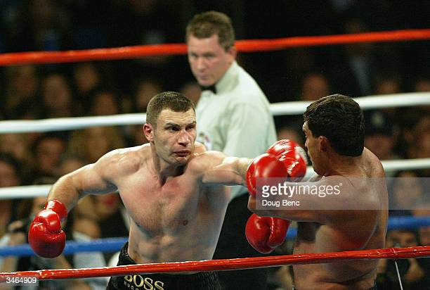 Vitali Klitschko lands a left to the chin of Corrie Sanders as referee Jon Schorle watches during a bout for the vacant WBC Heavyweight Championship...