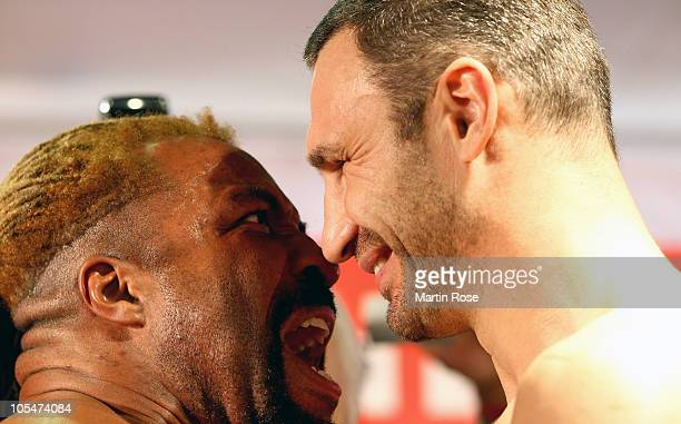 Vitali Klitschko of Ukraine and Shannon Briggs of USA looks at each other during the weigh in at Karstadt Sport on October 15 2010 in Hamburg Germany...