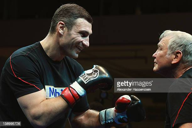 Vitali Klitschko of Ukraine exchange punches with his coach Fritz Sdunek during a public training session at Mercedes Benz show room on February 15...