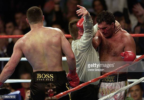 Vitali Klitschko walks away as referee Jon Schorle holds Corrie Sanders and stops the fight as in the 8th round of their WBC Heavyweight Championship...