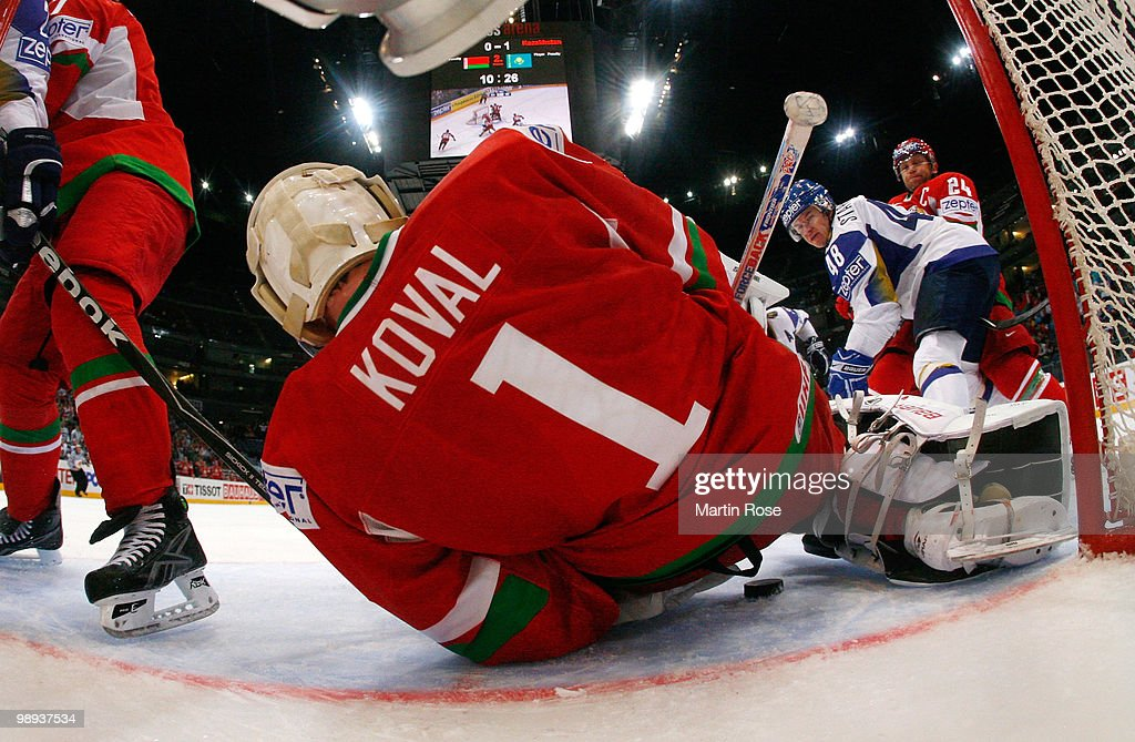 Vitali Koval, goalkeeper of Belarus saves the shot of Roman Starchenko of Kazakhstan battle for the puck during the IIHF World Championship group A match between Slovakia and Russia at Lanxess Arena on May 9, 2010 in Cologne, Germany.