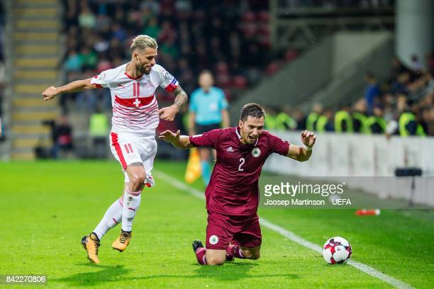 Vitalijs Maksimenko of Latvia is fouled by Valon Behrami of Switzerland during the FIFA 2018 World Cup Qualifier between Latvia and Switzerland at...