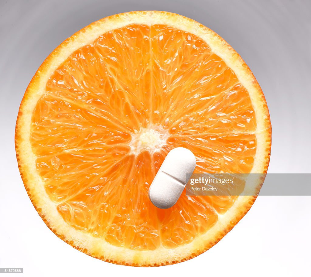 Vitamin C pill/ tablet on orange slice