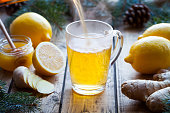 Vitamin black tea with ginger, lemon and honey poured in a cup with steam on a wooden table vintage. Healthy drink. Hot winter beverage concept. Antiviral useful drink.